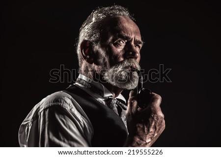 Pipe smoking vintage characteristic senior man with gray hair and beard. Studio shot against dark background.