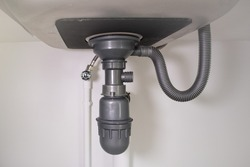 Pipe under kitchen sink. Consist of stainless steel, concrete counter, pvc plastic pipe, faucet, trap. Part of drainage and plumbing system. For water or sewer drain, siphon, repair and maintenance.