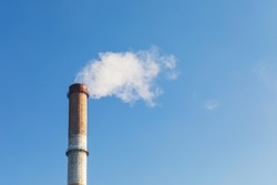 Pipe with white smoke against the background of blue sky and copy space