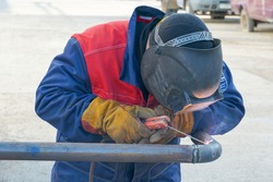 Pipeline, butt weld, electric arc welding, Welder welds the pipe. Manual arc welding of technological pipelines DN50 for an oil refinery in Russia