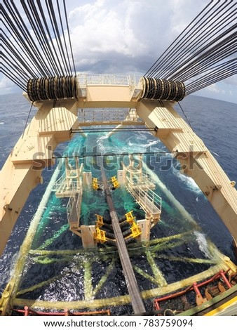 Pipeline exiting pipe tunnel over stinger of pipelay barge into the sea