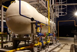 Pipeline system at a gas production and processing plant. Pipes, valves, manometers. Night shooting