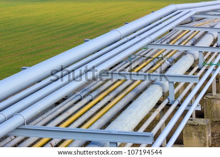 Pipeline tubes on green field - stock photo