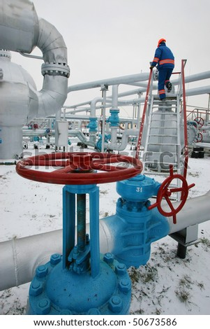 pipeline with tap in winter with worker
