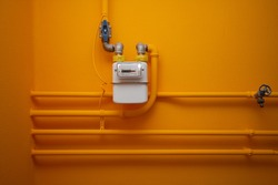 Pipes and gas-meter on orange wall
