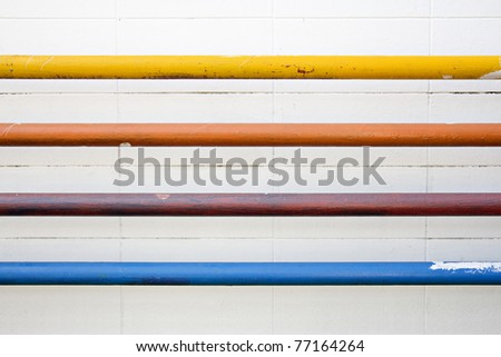 pipes of different color on white wall.