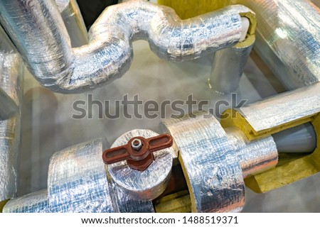 Pipes with a layer of insulating material and foil. Pipes with brown valve. Foil insulation for pipes. Demonstration of thermal insulation properties of insulation with foil.