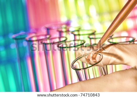 Pipette filled with red chemical and drop of liquid over laboratory glass test tubes in scientist hand for a chemistry experiment in a science research lab
