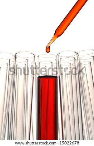 Pipette with drop of red liquid over test tubes for an experiment in a science research lab