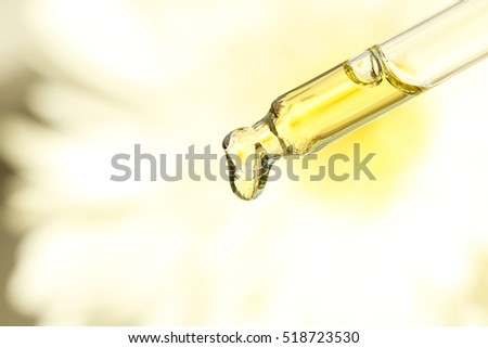 Pipette with essential oil on blurred flower background
