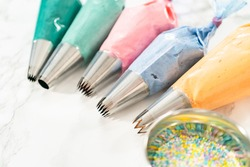 Piping bag with metal tips filled with colorful Italian buttercream frosting.