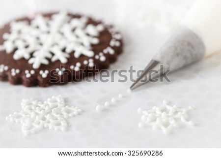Piping white snowflakes with royal icing, Selective focus.