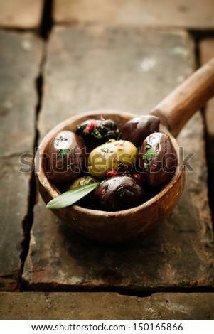 Piquant olives with a spicy chilli seasoning displayed in an old vintage wooden ladle or spoon on bricks with copyspace - stock photo