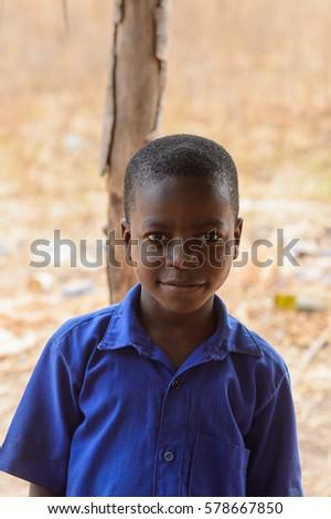 PIRA, BENIN - JAN 12, 2017: Unidentified Beninese little boy in a blue school uniform. Benin kids suffer of poverty due to the bad economy. #578667850