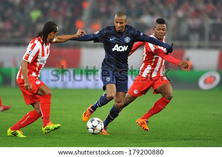 PIRAEUS, GREECE -FEB. 25. Olympiakos vs Manchester United 2-0. Manchester United\'s Ashley Young (center) battle for the ball  with Olympiakos\' Michael Olaitan (right) in Peiraeus, February 25, 2014