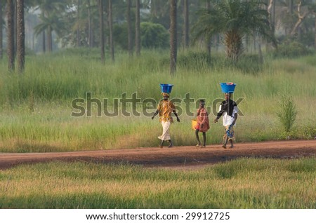PIRANG, GAMBIA - OCTOBER 31 : 2 women and a boy carry laundry on October 31, 2008 in Pirang, Gambia. The women are using the traditional method carrying the baskets on their heads. - stock photo