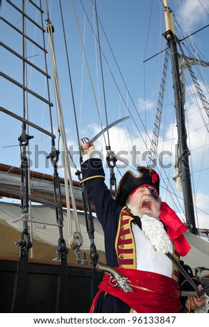 Pirate captain in colorful traditional costume stands on board ship, shouts, and waves his sword. Sailing ship rigging and blue sky in background, vertical layout.