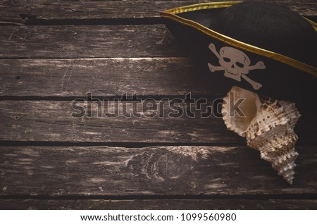 Pirate captain table concept background with copy space. Pirate hat and seashall on old wooden board.