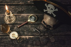 Pirate captain table with pirate hat on the human skull, compass, magnifying glass, mooring rope, coins, key of treasure chest and burning table. In the searching of gold.