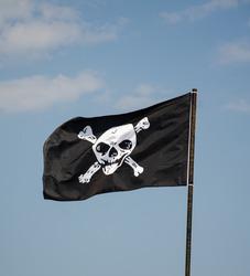 Pirate flag against the blue sky, skull and bones, jolly roger.