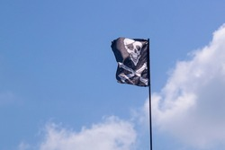 pirate flag develops in the wind, skull with bones, Jolly Roger,the symbol of the robbery