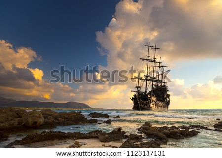 Pirate ship at the open sea at the sunset
