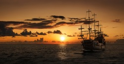 Pirate ship at the open sea at the sunset with copy space