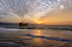Pirate ship fantasy is an old wooden boat with full flags as the sun sets on the ocean and the moon rises in a colorful sky.