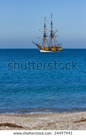 Pirate Ship off Shore in Tropical Water with beach in foreground