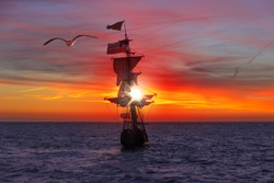 Pirate ship sailing toward the sun rising over the horizon following by a seagull in the air