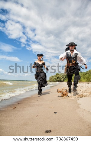 Pirates a man and a woman run along the sandy shore - Shutterstock ID 706867450