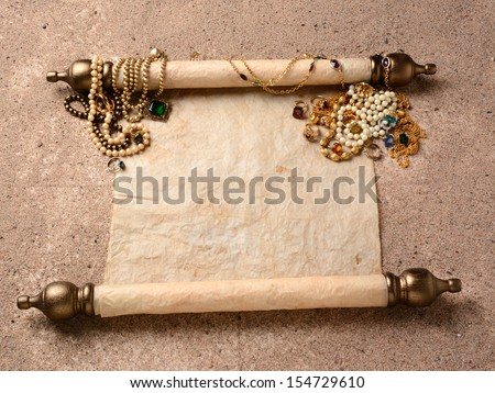 Pirates Booty. An ancient scroll laying on beach sand with jewelry scattered on it upper end. The scroll is blank ready for your treasure map or copy.