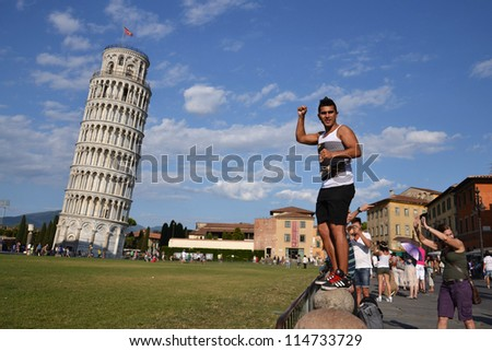 PISA, ITALY - JULY 16: Tourist posing in front of the Leaning tower of Pisa on July 16 2012 in Pisa, Italy. The Leaning Tower is one of the landmarks available in new 45�° imagery in Google Maps.