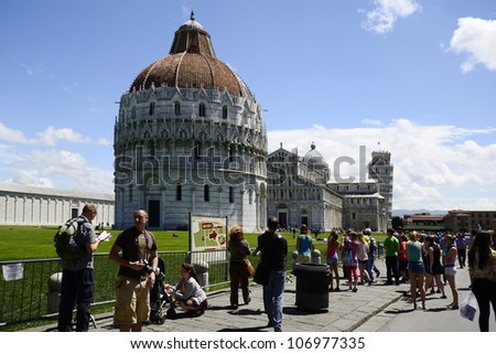 PISA, ITALY - JUNE 11: tourists on Piazza dei Miracoli with Dome Santa Maria Assunta, Leaning Tower and Battistero di San Giovanni, a Unesco World Heritage site on June 11, 2012 in Pisa, italy