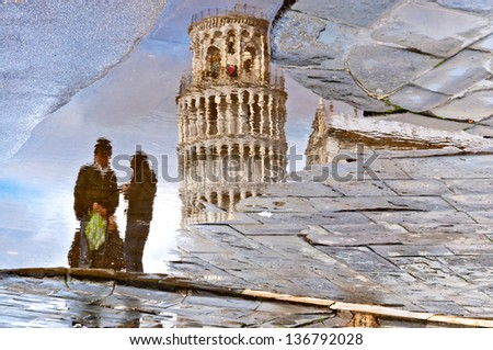 PISA, ITALY - MARCH 18: reflection of the leaning tower and couple of unidentified tourists in a puddle on March 18, 2013 in Pisa.Place of Miracles is a UNESCO World Heritage Site since 1987