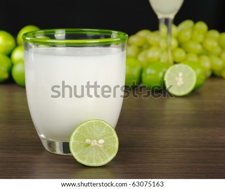 Pisco Sour, a Peruvian cocktail from grape liquor, sugar syrup, lime juice and egg white (Selective Focus, Focus on the front rim of the glass and the half of a lime)