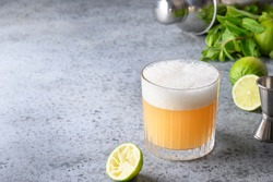 Pisco sour cocktail - whiskey with lime, egg white, sugar syrup in glass on grey stone table. Space for text.