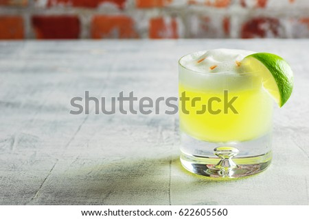 Pisco Sour Cocktail with Lime in Rocks Glass on Bar with Copy Space/Room for Text