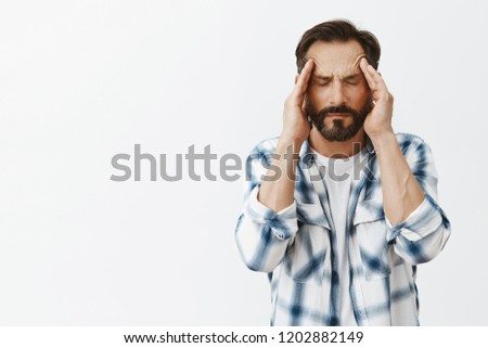 Pissed off man trying control anger, massaging temples with closed eyes, trying calm down, feeling headache or suffering from migraine, having bad day and asking for painkillers over gray background #1202882149