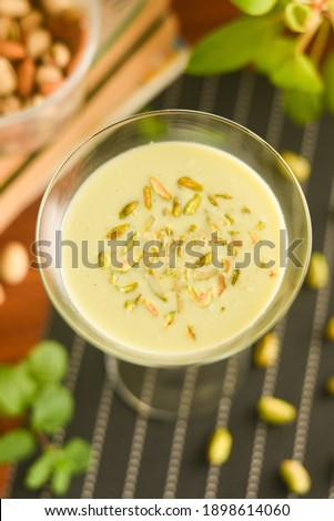 Pista Badam milk shake or Almond Pista milk Kerala India. Woman taking glass of pistachio milk with hand. Kheer or North Indian traditional health drink Flavoured milk or badam lassi with dry fruits.