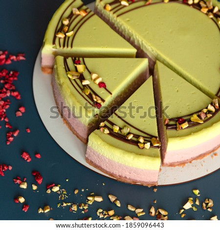 Pistachio and raspberry cheesecake decorated with chocolate and beans. Dark blue background. green and pink cheesecake portion cutting dessert closeup  Stock photo ©
