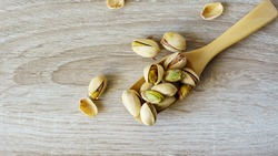 Pistachio nuts are in a wooden spoon placed on a wooden table.