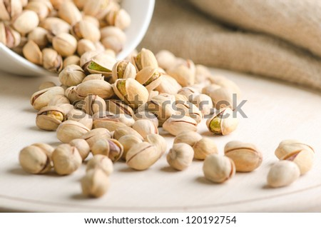 Pistachio nuts just falling on a wooden board