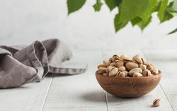 Pistachios in a bowl on a light wooden table with green leaves in the background. Healthy snacks. Nuts. Copy space.