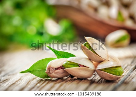 Pistachios nuts on wooden table. Pistachio in wooden bowl in background with green leaves.