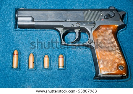 pistol and four bullets in blue box