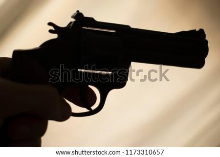 Pistol automatic handgun weapon in silhouette in hand of killer atmospheric dark dramatic photo.