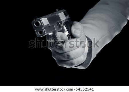 Pistol in hand on a black background