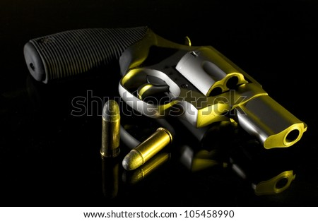 Pistol on black with two cartridges with yellow lighting from the side