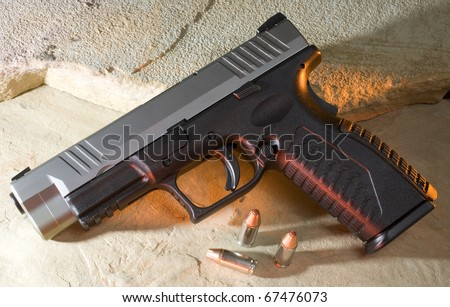 Pistol on rock that has red and yellow gels on it